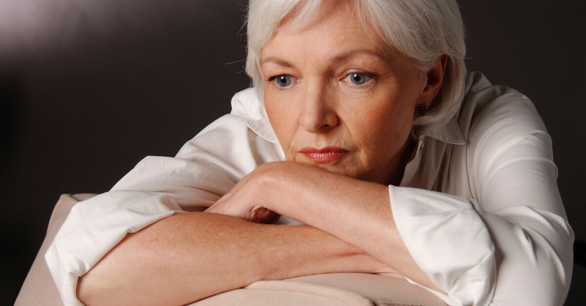 elderly woman resting her chin on her arms looking sad or in deep thought