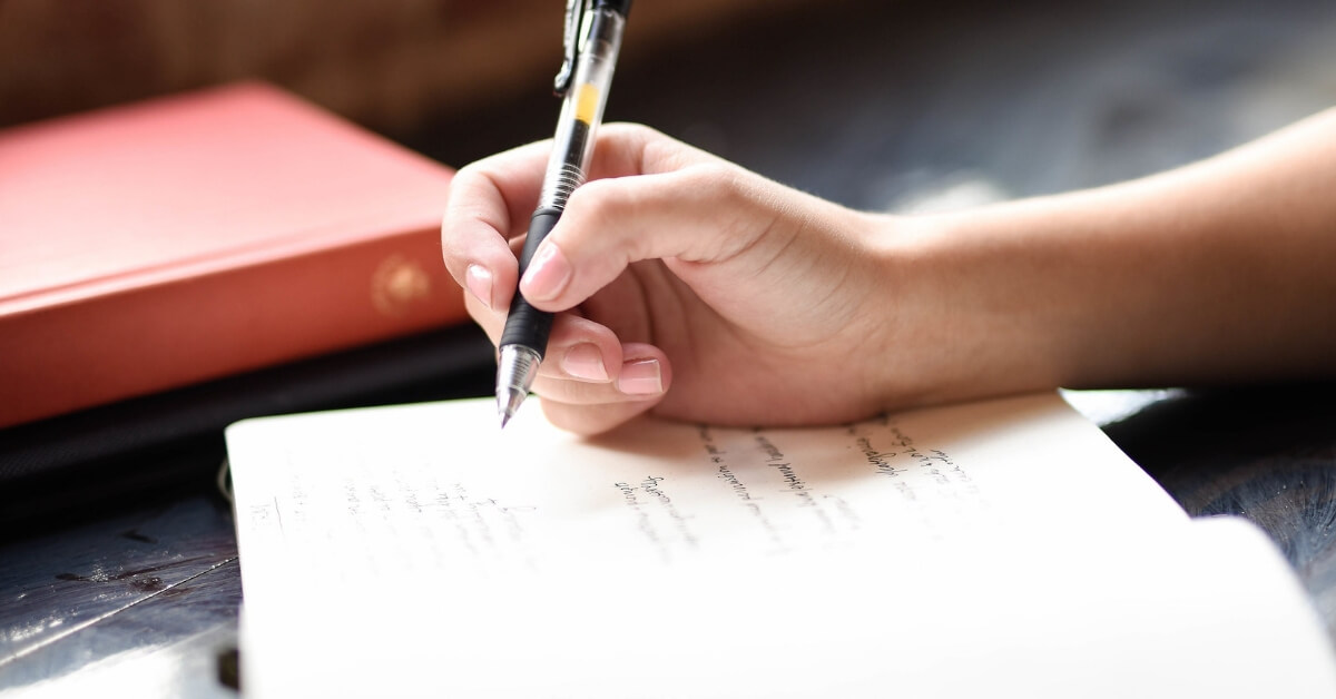 a person's hand writing in a notebook
