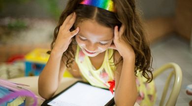 young girl smiling at an iPad-2
