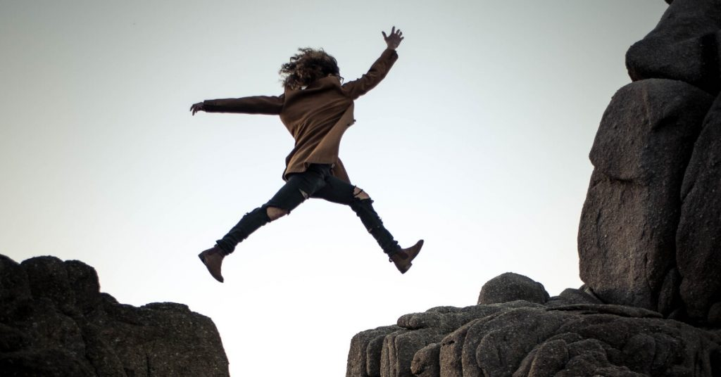 person leaping from one rock to another
