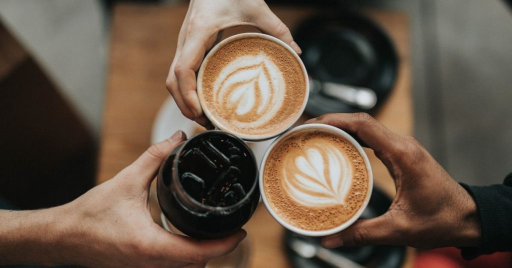 3 people holding coffee cups